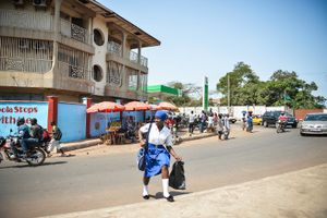 A young woman crosses the road after returning from school.