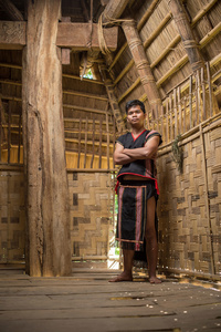 To Dra young man inside the communal house in Kon Tum Province