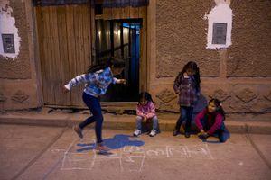 Girls play hopscotch on the streets of Calca, Cusco, Peru