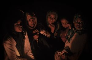 A group of young girls sit together in a small group around a lamp during one of Sanaa's frequent power cuts.