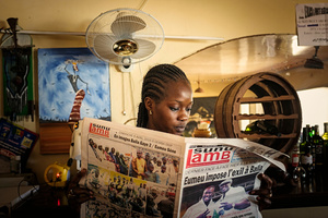 "Dakar, April 9, 2015. Even young girls like Aissa (23), the waitress of the ""Black and White"" bar on the beach of Ngor, read the newspaper ""Sunu Lamb"" as well, which daily publishes exclusively Senegalese wrestling matches."