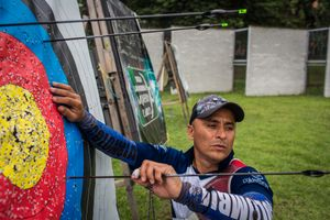 German Gomez, 49, collects the arrows from the target sign during a practice session at the Belen Sports Complex, Medellin, April 2016.