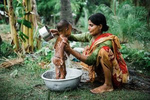 Amina getting a bath back home in the countryside. Basanti, West Bengal, India. June 7th 2019
