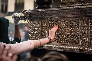 Many people touch the pasos as part of their prayers.