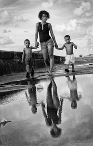 Fraternal twins walking on the Malecon with their mother.