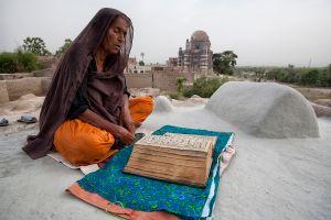 Uch Sharif, Pakistan: A woman praying on a grave of her husband. © Matjaz Krivic