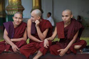 Three monks lounging at the Shwedagon Pagoda