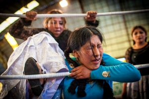 Juanita La Cariñosa punishes Jennifer Dos Caras on the ropes during a fight in the 12th October Sports Complex in El Alto.