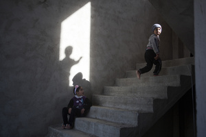 Children play on an unfinished staircase inside the building where they have been living with their families since August 2014, when they escaped from Sinjar. 01/02/15. Sitak, Iraq.