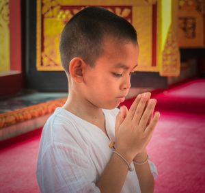 Young Buddhist offering prayers at a Buddhist Temple, Bangkok, Thailand.