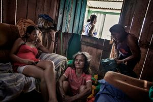 Donna Maura, 55 years old, is sitting on the floor of Patricia's house in 'Invasao dos Padres'. After loosing everything, she's been somehow adopted by her and contribute by cleaning the clothes of the family. On the left Eugenia, 23 years old, is waiting for her boyfriend to call her. Her ex-husband is in jail charged with homicide. © Dario Bosio/Parallelozero