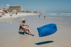 An old woman sitting on a lounge chair on Ormond beach watches a bodyboard go by. Daytona Shores, Florida.