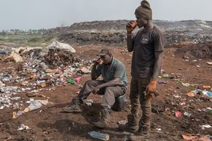 Two waste pickers are having a break after searching through a truck load of waste. A whole economy has developed in Mbeubeuss, not only waste pickers and traders work here but also vendors who sell coffee or food.