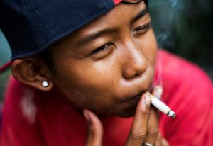 """Ompong, which means """"toothless"""", poses for a photograph as he has a cigarette in South Jakarta, Indonesia. © Michelle Siu"""