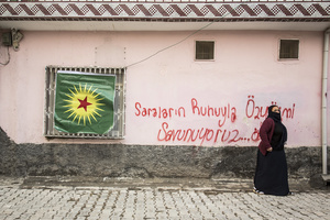 Woman stands in front of Kurdish KCK flag in Kurdish-dominated city of Nusaybin in southeast Turkey, near the Syrian border. Heavy gunfights took place during several curfews between Turkish government special forces and Kurdish YPS guerilla fighters.