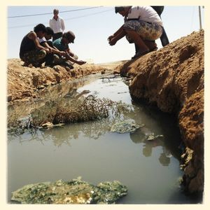 Michael and the boys take pictures at a waste water stream which runs through the camp