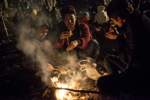 Three migrants having dinner next to campfire made from the trees nearby, at Spiefeld refugee camp, Austria.