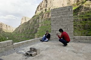 These two Kurdish tourists take photos and selfies in an abandoned construction site next to Hamilton Road near Khalifan. © Tom Verbruggen