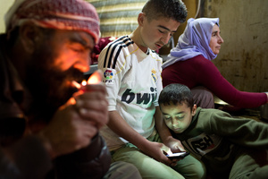 Saïd lights a cigarette while Ezidiar, 9, looks at Serdesht's, 13, phone and Ghazal watches television.The family of Yezidis, displaced from Sinjar, live next to an oil refinery in the Kurdish region of Iraq. The young men run the refinery 24 hours a day with little to no safety equipment. 18/02/15