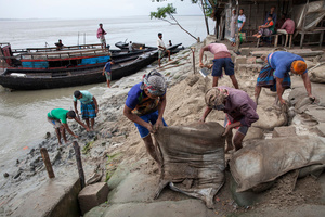 People work to repair the embankment designed to protect their island from river erosion. Satkhira, Bangladesh