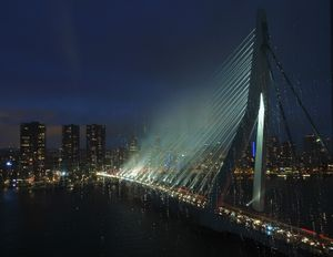 Here we see the whole picture. A  white fog  is formed where the bridge's  illumination reflects against the raindrops.