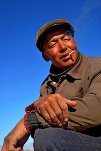 Mongolian eagle hunter smoking.