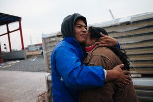 A Honduran immigrant couple embraces next to the railroad while waits for the train, in Mexico City, May 20, 2008.