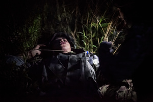 A volunteer come to the rescue of a wounded soldier, in a overnight training.