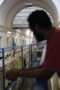 An inmate looks over the wing outside of his cell on the top balcony of the A wing at Wandsworth Prison. HMP Wandsworth in South West London was built in 1851 and is one of the largest prisons in Western Europe. It has a capacity of 1456 prisoners.