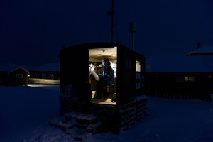 Senior scientist of Norwegian Institute working in a small research cabin for measuring CO2 in Ny Alesund settlement