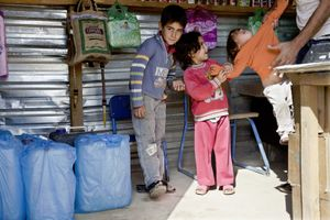 A father and his three children in the family's food shop in Zaatari's main street. © Tom Verbruggen