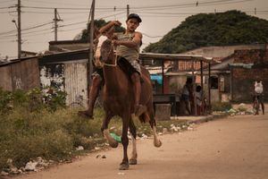 A young teenager rides a horse on one of the main streets on the east side of the river in City of God. Despite its size, City of God's educational system consists of one high school that provides evening classes. © Manu Valcarce