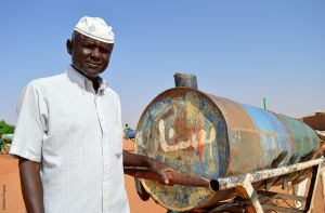 Man next to his donkey cart for water transportation