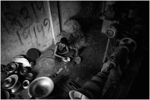 A boy has his lunch at a corner of the factory.