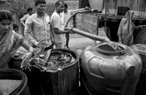 A woman splashes water to clean a water drum as other villagers fill up a drum for later use, Maharashtra 2016. Washing clothes, crockeries and bathing have become a luxury for the drought hit villagers.