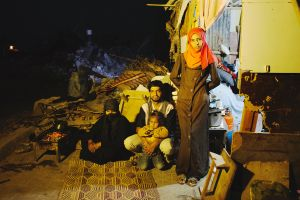 Fadla Al-Najar, 63, and his 30 year old son Osama and her 2 year old grand-daughter Habiba, and Osama' s 26 year old wife Taghreed, on the right, saw their home in Khoza'a in Khan Yunis destroyed by Israel Defense Forces during the summer's 50-day war. They still stay in a tent on the site of the damaged home. Despite the difficulty, they cannot leave, since there is no place else to move in.
