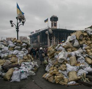 Back of female civilian between  towering barricades facing burned Euromaidan political headquarters, February 2014.