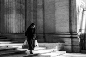 Nun carrying bags