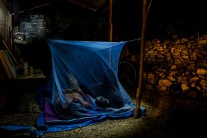 Allan, community youth leader of Paga Hill and his friend Frank are sharing this mosquito net. Their family homes were demolished on May 12, 2012.