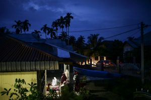 A survivor pray after evening prayer outside of her house as she traumatized to not be in the house following the earthquake in Pidie Jaya, Aceh province, on December 11, 2016.