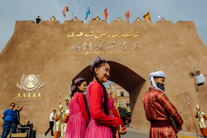 A performers waiting to doing a performance for tourist at the outside of the new Kashgar Old City gate.