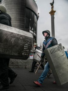 Anti-government protesters marching through Independence Square with makeshift shields for protection, February 2014.