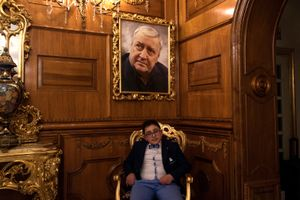 """A guest poses in the hall of """"Grand Hotel La Sonrisa"""", below the photo of Mario Merola, a very famous singer from Naples in the 70's."""