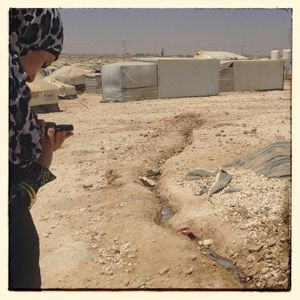 Nour* takes  picture of a waste water stream running through the camp