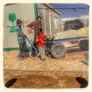 Children move gravel around the camp during the heat of the day