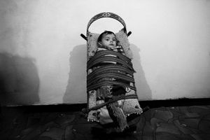 Islam, a 14-month old baby in his cradle. Tirana, Albania © Enri Canaj