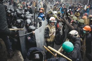 Volunteer of the Red Cross tries to stop protesters and do not to let them to beat the police.  Kiev, Feb. 20, 2014