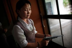 A North Korean woman loads a pistol for firing practice in Pyongyang, North Korea on August 18th, 2007.