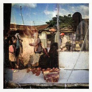 A street scene reflected in the window of a butcher's in Kibera. The Kibera slum is the largest slum in Nairobi with around half a million inhabitants.