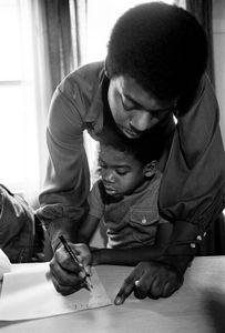 1972 - Berkeley, California, USA: Austin Allen helps Malik Seale, Bobby's son, write at the Intercommunal Youth Institute. (Stephen Shames/Polaris)The Children's House, The Intercommunal Youth Institute and the Oakland Community School.